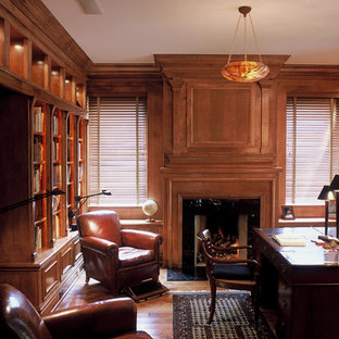 Home office library - traditional freestanding desk medium tone wood floor home office library idea in Indianapolis with a standard fireplace and a wood fireplace surround