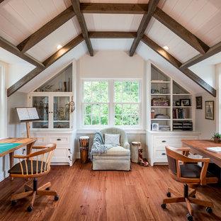 Cette photo montre un grand bureau nature de type studio avec un mur gris, un sol en bois brun, un bureau indépendant et un sol marron.