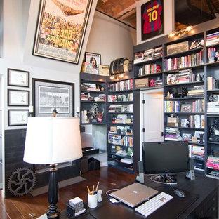Bild på ett mellanstort industriellt hemmabibliotek, med vita väggar, mellanmörkt trägolv, en spiselkrans i metall och ett fristående skrivbord