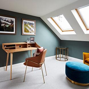 ロンドンのトランジショナルスタイルのおしゃれなホームオフィス・書斎 (緑の壁、カーペット敷き、自立型机、グレーの床、三角天井) の写真