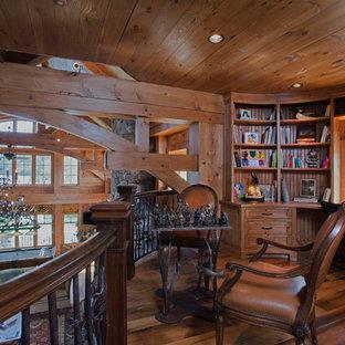 Bild på ett stort rustikt arbetsrum, med ett bibliotek, bruna väggar, mellanmörkt trägolv och ett inbyggt skrivbord