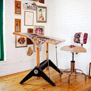 Imagen de estudio bohemio con paredes blancas, suelo de madera en tonos medios y escritorio independiente