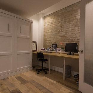 トロントの小さいコンテンポラリースタイルのおしゃれなホームオフィス・書斎 (ライブラリー、白い壁、ラミネートの床、造り付け机、茶色い床) の写真