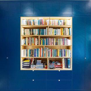 Esempio di un grande ufficio minimalista con pareti blu, pavimento in laminato, scrivania incassata e pavimento blu