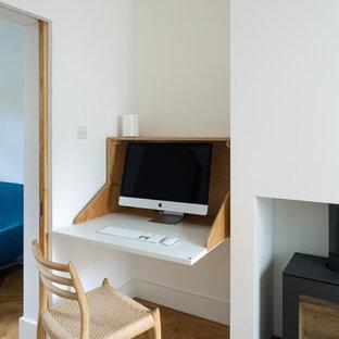 ロンドンの小さいエクレクティックスタイルのおしゃれなホームオフィス・書斎 (白い壁、淡色無垢フローリング、薪ストーブ、茶色い床) の写真