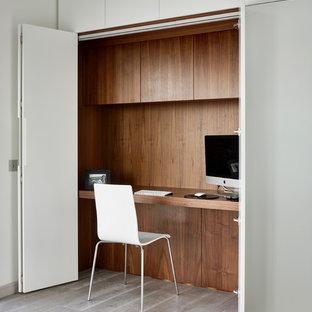 Foto di un ufficio minimal con scrivania incassata, pareti multicolore e parquet chiaro