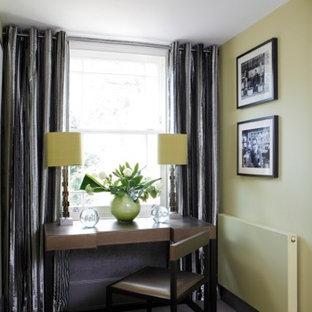 Esempio di un piccolo studio bohémian con libreria, pareti gialle, moquette, scrivania autoportante e pavimento marrone