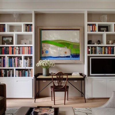 Home office library - transitional freestanding desk light wood floor home office library idea in London with gray walls
