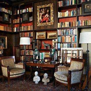ロンドンの広いトラディショナルスタイルのおしゃれなホームオフィス・書斎 (赤い壁、自立型机、濃色無垢フローリング、ライブラリー) の写真