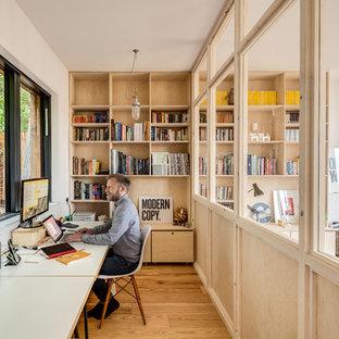 Exempel på ett litet nordiskt hemmastudio, med vita väggar, mellanmörkt trägolv, en öppen vedspis och ett inbyggt skrivbord