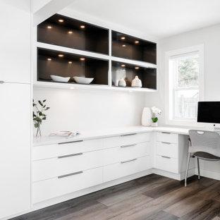 Foto di uno studio minimalista di medie dimensioni con pareti bianche, pavimento in vinile, camino classico, cornice del camino in intonaco, scrivania incassata e pavimento marrone