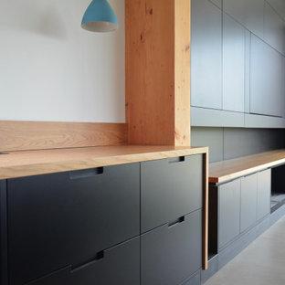 Idée de décoration pour un bureau vintage de taille moyenne avec un mur gris, un sol en carrelage de porcelaine, une cheminée ribbon, un manteau de cheminée en métal, un bureau intégré et un sol gris.