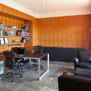 バンクーバーの大きいコンテンポラリースタイルのおしゃれなホームオフィス・書斎 (茶色い壁、スレートの床、暖炉なし、自立型机、グレーの床) の写真