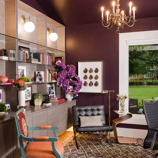 This is an example of an eclectic home office and library in Other with purple walls and medium hardwood flooring.