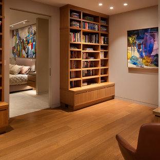 サンフランシスコの中サイズのコンテンポラリースタイルのおしゃれなホームオフィス・仕事部屋 (ライブラリー、グレーの壁、無垢フローリング、暖炉なし、自立型机、茶色い床) の写真