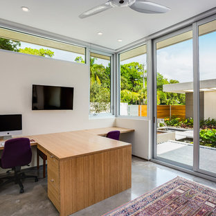Mid-sized trendy freestanding desk concrete floor study room photo in Tampa with white walls and no fireplace