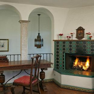 ロサンゼルスのサンタフェスタイルのおしゃれなホームオフィス・書斎 (ベージュの壁、濃色無垢フローリング、コーナー設置型暖炉、タイルの暖炉まわり、自立型机) の写真