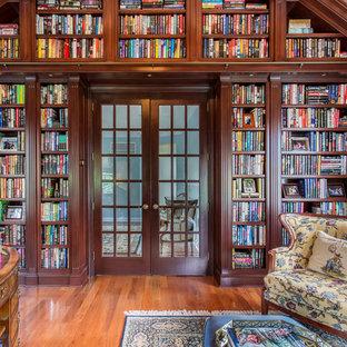 Bild på ett stort vintage arbetsrum, med mellanmörkt trägolv och ett bibliotek