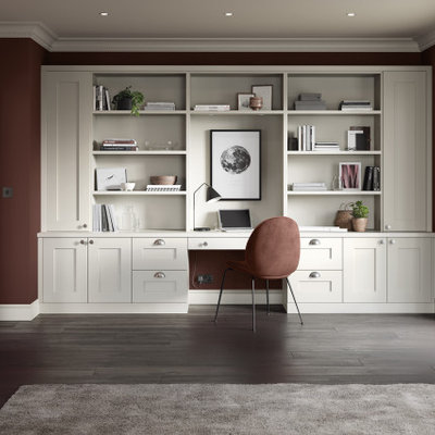 Example of a mid-sized classic built-in desk medium tone wood floor and brown floor study room design in Manchester with red walls