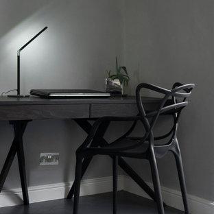 Immagine di un ufficio contemporaneo di medie dimensioni con pareti grigie, pavimento in legno verniciato, scrivania autoportante e pavimento grigio