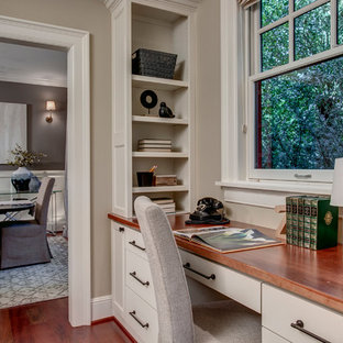 Example of a small transitional built-in desk medium tone wood floor and beige floor home office library design in Seattle with beige walls