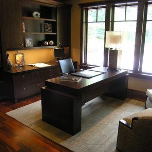 Foto di un grande studio minimal con pareti gialle, parquet scuro e scrivania autoportante