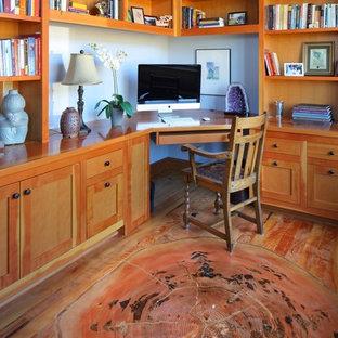 Aménagement d'un petit bureau craftsman avec un mur blanc, un sol en bois brun et un bureau intégré.