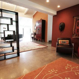 オレンジカウンティの大きいミッドセンチュリースタイルのおしゃれな書斎 (赤い壁、コンクリートの床、暖炉なし、自立型机) の写真