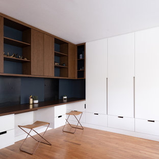 Design ideas for a medium sized modern study with white walls, light hardwood flooring, a standard fireplace, a metal fireplace surround and a built-in desk.