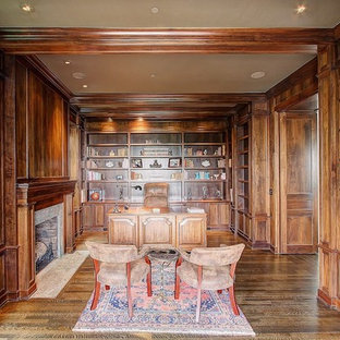 Design ideas for an expansive arts and crafts study room in Seattle with brown walls, dark hardwood floors, a standard fireplace, a stone fireplace surround and a freestanding desk.