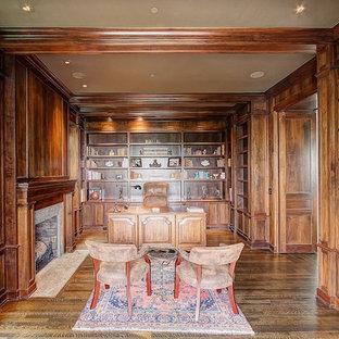 Idee per un ampio ufficio american style con pareti marroni, parquet scuro, camino classico, cornice del camino in pietra e scrivania autoportante
