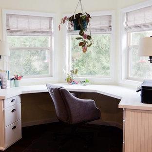 Immagine di un piccolo studio country con pareti gialle, parquet scuro, scrivania incassata, nessun camino e pavimento marrone