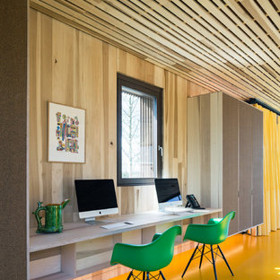 Example of a mid-sized eclectic built-in desk linoleum floor and yellow floor study room design in London with brown walls