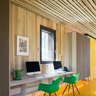 ロンドンの中サイズのエクレクティックスタイルのおしゃれな書斎 (茶色い壁、リノリウムの床、造り付け机、黄色い床) の写真
