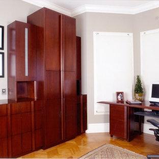 Exempel på ett mellanstort modernt hemmabibliotek, med grå väggar, ljust trägolv och ett fristående skrivbord