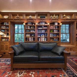 Foto di uno studio american style con libreria, pareti marroni, parquet scuro, scrivania autoportante e pavimento marrone