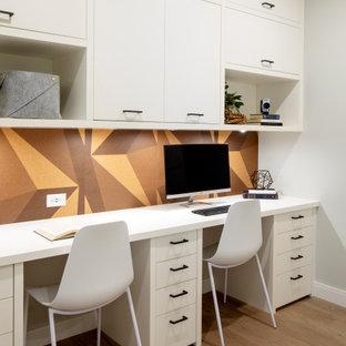 バンクーバーのコンテンポラリースタイルのおしゃれな書斎 (マルチカラーの壁、淡色無垢フローリング、暖炉なし、造り付け机、ベージュの床) の写真