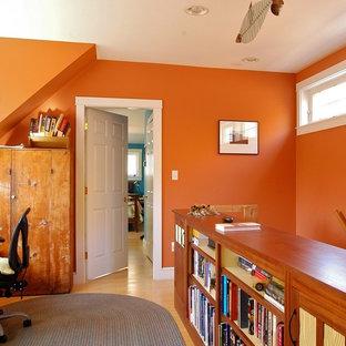 ポートランド(メイン)の中くらいのエクレクティックスタイルのおしゃれなホームオフィス・書斎 (オレンジの壁、無垢フローリング、造り付け机、暖炉なし、茶色い床) の写真