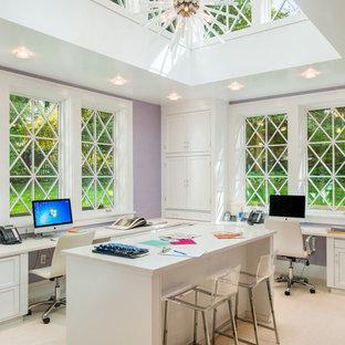Klassisk inredning av ett hemmastudio, med lila väggar, heltäckningsmatta, ett inbyggt skrivbord och beiget golv