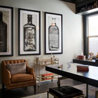 Неиссякаемый источник вдохновения для домашнего уюта: большое рабочее место в классическом стиле с бежевыми стенами, темным паркетным полом и отдельно стоящим рабочим столом без камина