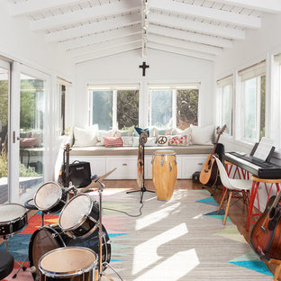 Home studio - mid-sized beach style medium tone wood floor home studio idea in Los Angeles with white walls