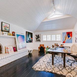 ロサンゼルスの巨大なエクレクティックスタイルのおしゃれなアトリエ・スタジオ (白い壁、標準型暖炉、レンガの暖炉まわり、自立型机、黒い床、濃色無垢フローリング) の写真