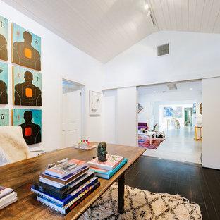 Idee per un ampio atelier boho chic con pareti bianche, camino classico, cornice del camino in mattoni, scrivania autoportante, parquet scuro e pavimento nero