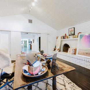 Immagine di un ampio atelier eclettico con pareti bianche, camino classico, cornice del camino in mattoni, scrivania autoportante, parquet scuro e pavimento nero