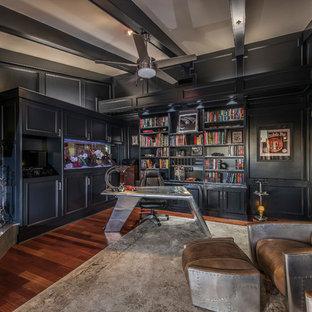 Ejemplo de despacho actual con paredes negras, suelo de madera oscura, chimenea de esquina, marco de chimenea de baldosas y/o azulejos, escritorio independiente y suelo marrón