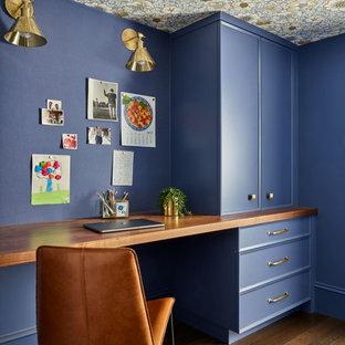 Пример оригинального дизайна: большое рабочее место в стиле современная классика с синими стенами, паркетным полом среднего тона, встроенным рабочим столом, коричневым полом, потолком с обоями и панелями на части стены без камина