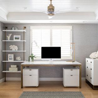 Bild på ett mellanstort maritimt arbetsrum, med grå väggar, ljust trägolv, en spiselkrans i sten, ett fristående skrivbord och beiget golv