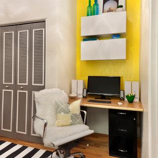 Immagine di un piccolo studio contemporaneo con pavimento in legno massello medio, scrivania autoportante e pareti multicolore