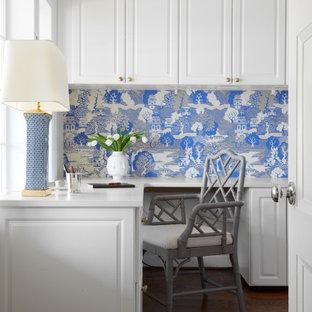Exemple d'un bureau chic avec un sol en bois brun, un bureau intégré, un sol marron, un mur bleu et du papier peint.