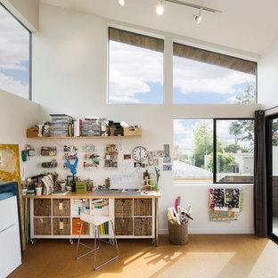 Idéer för ett litet modernt hemmastudio, med korkgolv, brunt golv, vita väggar och ett fristående skrivbord